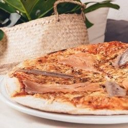 Donostia san sebastian Thin-crust pizza with mozzarella, tomato, salmon and smoked anchovies and oregano
